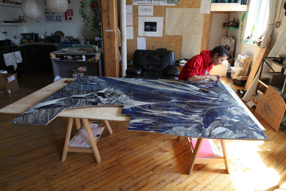 Carving the linoleum flooring from Peter Pitseolak School that was salvaged from the Kinngait (Cape Dorset) dump in 2015. 1 year later Peter Pitseolak School was destroyed by fire.
