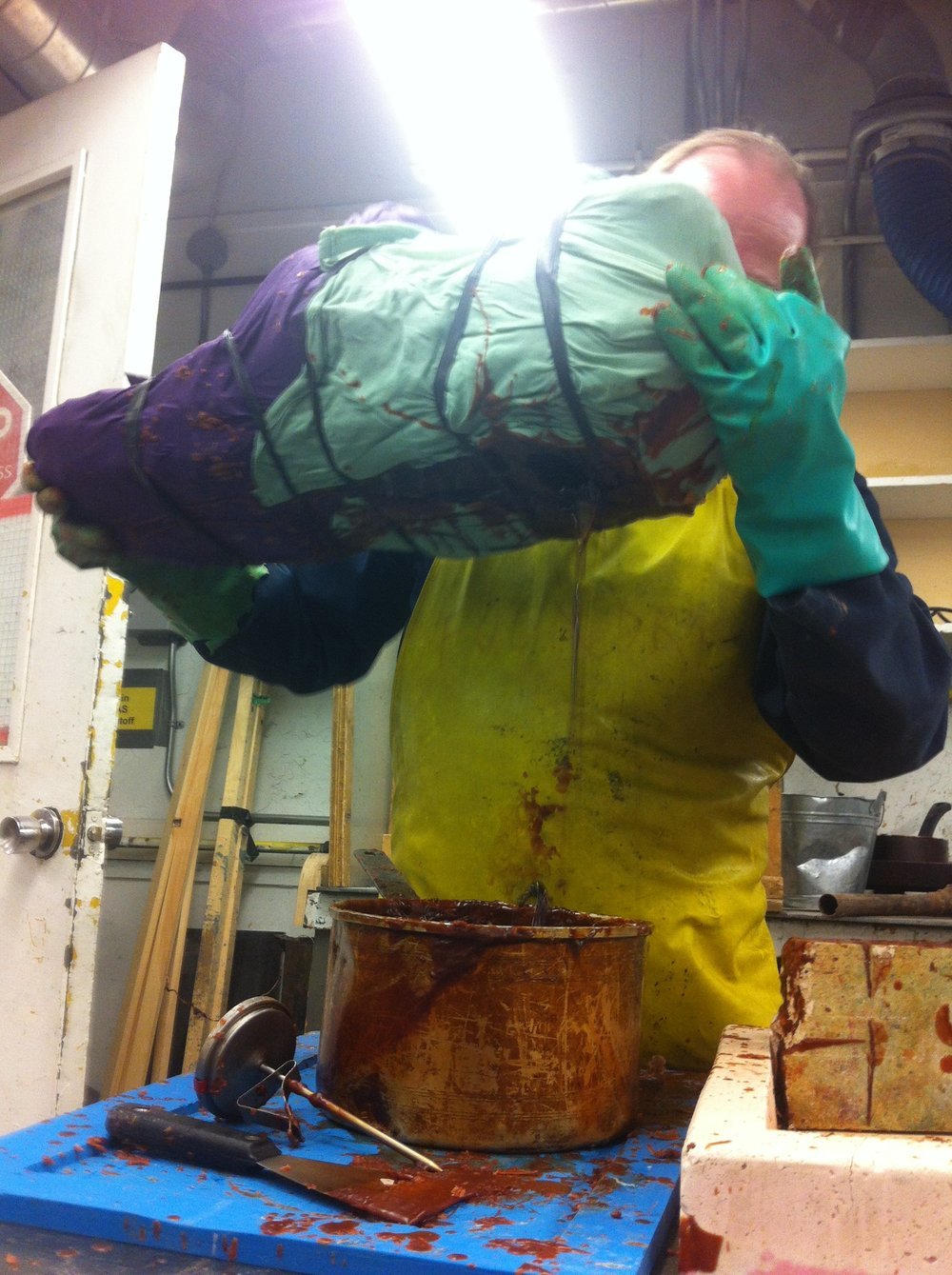 George Farmer (Foundry Technician OCADU) slushes wax into Moe Kelly and David Pudlat's mother mould.