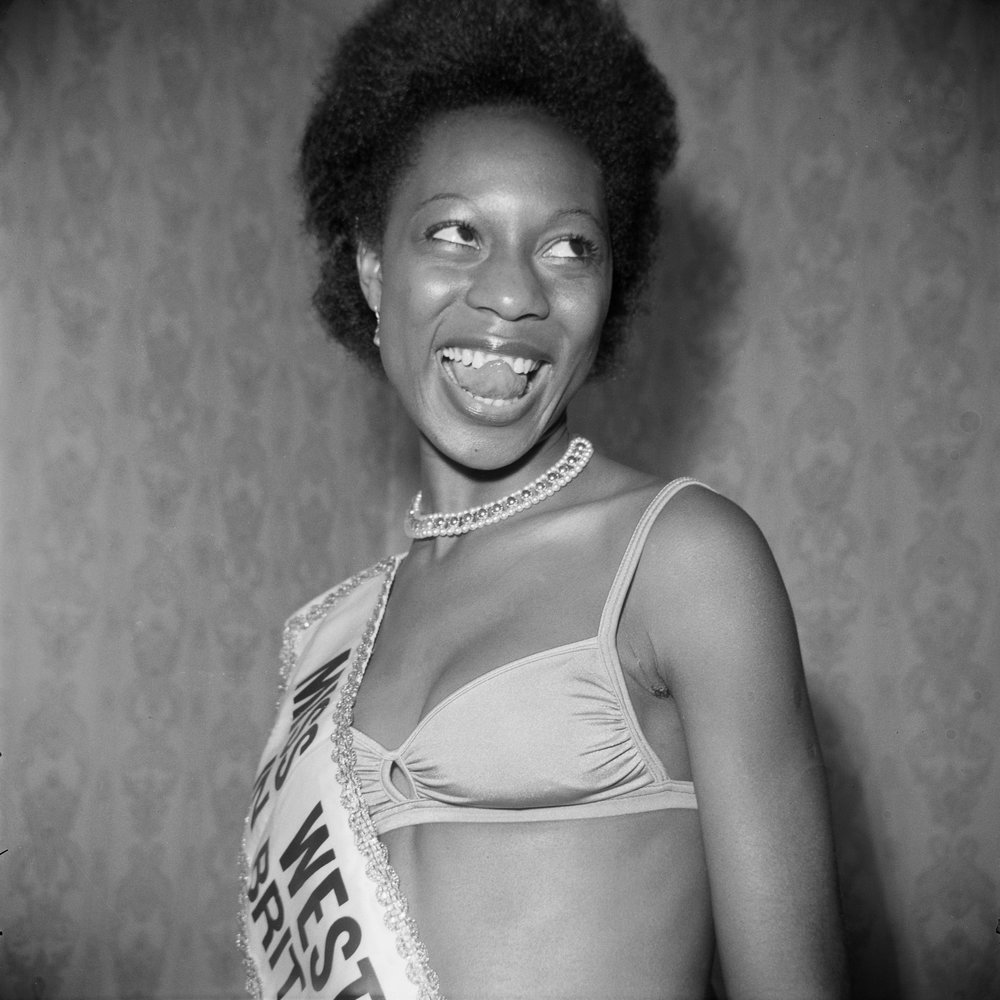 (Unidentified) Miss West Indies in Great Britain contestant posing at Blythe Road, Hammersmith, London, 1970s. From the portfolio 'Black Beauty Pageants'. Courtesy of © Raphael Albert/Autograph ABP