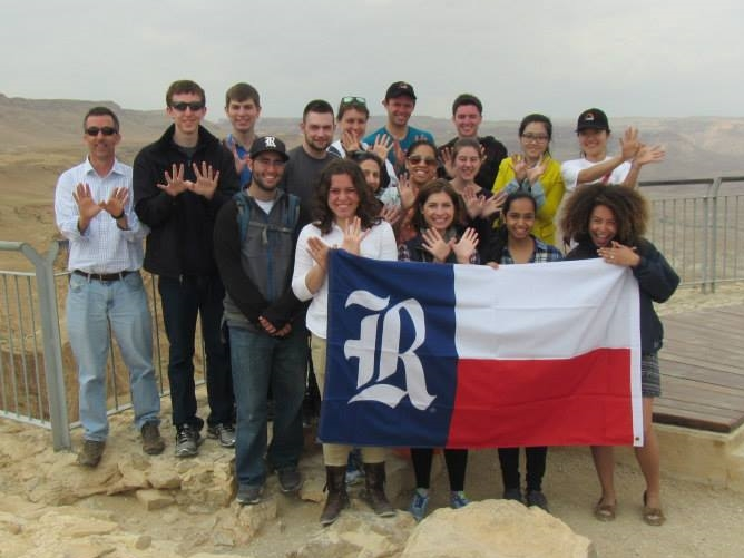 Picture of the class with professors and students holding a Rice University flag.