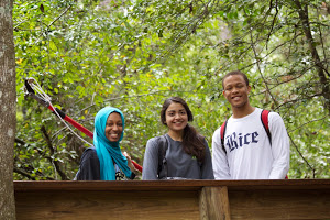 Three students smiling in the woods.