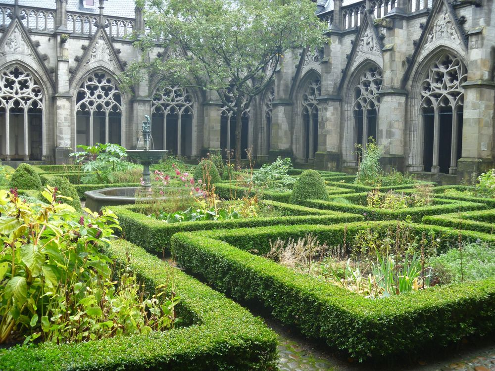 The cloister garden of Sint Agathaklooster is completely enclosed,  contains a central sculptural feature and rectangular plots for herbal and decorative plants. 1300's CE. Utrecht, the Netherlands.