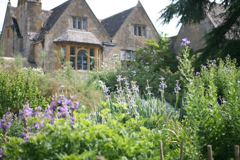 This view of an arts and crafts garden show the house being embraced by the plantings.  Though carefully planned and maintained, the result looks romantic and carefree.   Hidcote , Gloucestershire, UK. 1920's.