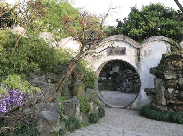 This moon gate at the  Humble Administrator's Garden  in Suzhou, China provides a clear opening to the next part of the garden. The narrowing paved stones and  even the direction of the leaning tree on the left point in the same direction.  The vertical rocks beyond the gate give us a teaser of what's to come.