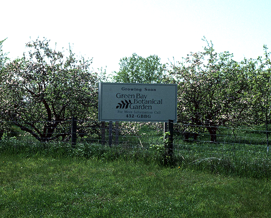 "Sign posted in front of the ""old Larsen orchard"" announcing that the botanic garden was coming soon, 1990's. Source:  The Green Bay Botanical Garden ."