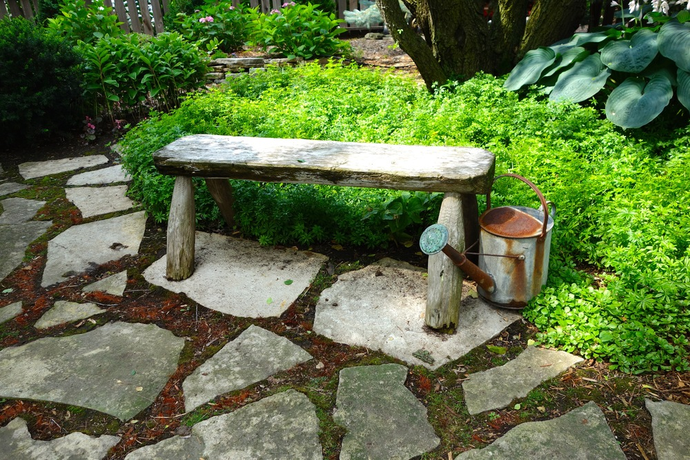 A bench in the woodland garden reinforces the rustic feel of this part of the property.