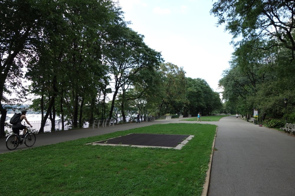 Paving and blocks of mowed grass cover the Serpentine Promenade.  Large metal grates allow air to escape from the train tunnel beneath.  The 91st Street Community Garden can be seen in the far distance.