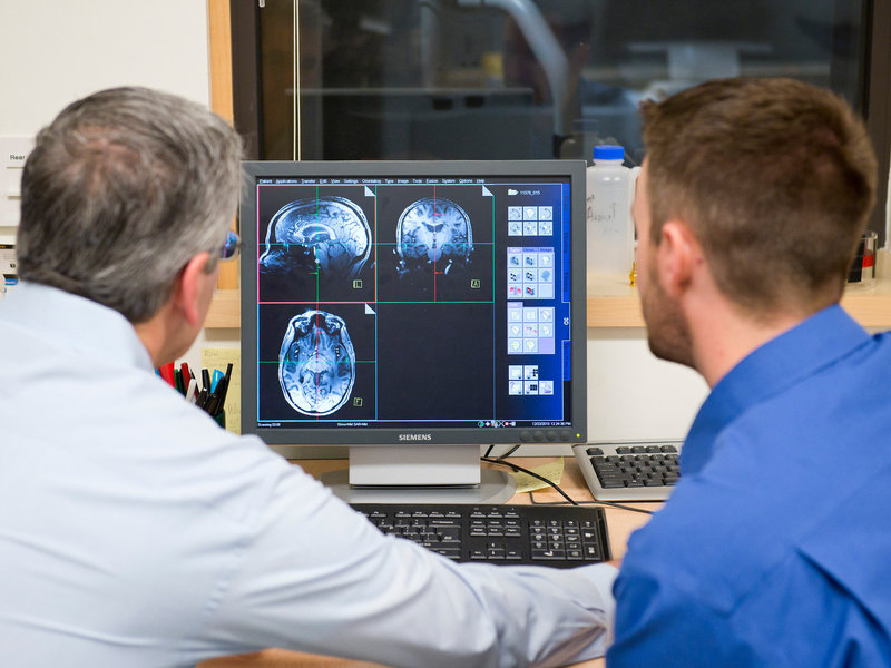 Jeffrey Iliff (right) and Bill Rooney, brain scientists at Oregon Health & Science University, look over an MRI. The school has an especially sensitive MRI unit that should be able to detect precisely when during sleep the brain is being cleansed of toxins.  Courtesy of Oregon Health & Science University