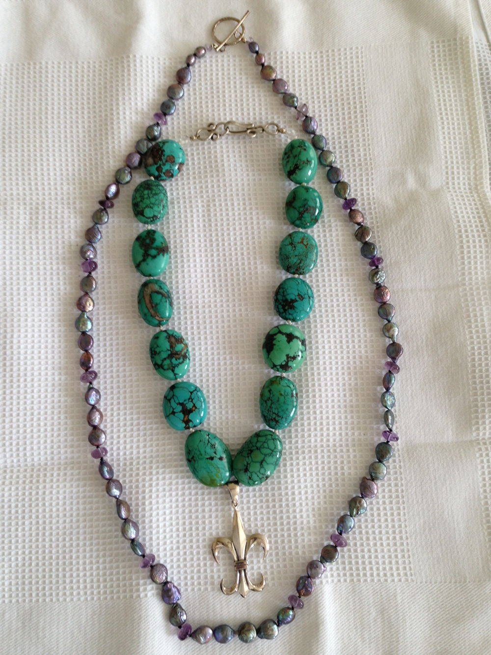 "20"" Turquoise necklace with sterling gold fleur de lis drop and sterling silver clasp knotted on silk cord. Freshwater peacock coin pearl necklace with amethyst rondells and sterling silver toggle clasp knotted on silk cord. Value: $500.00."