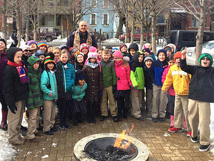 Fr. Larry and ICSJ 2nd Graders burn palm fronds.