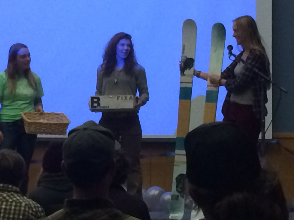 """Sami Bierman, Emma Kerins, Madde Gnauck raffling items at the Bozeman premiere of the ski film """"Pure,"""" which was also a coat and winter clothing drive for the local warming center."""