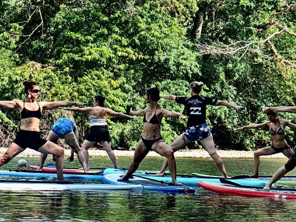 Heidi Michelle guiding SUP Yoga in Costa Rica. Surrounded by nature and the elements, feeling connected is  easy.