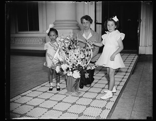 Eleanor Roosevelt is gifted a May Day basket. Photo via Library of Congress
