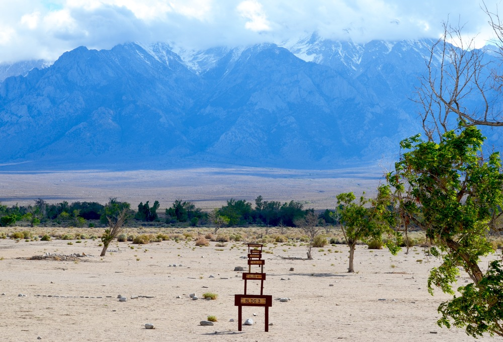 Markers tell visitors where Manzanar buildings once stood. Notice the snow capped peaks in the Sierra Nevada mountains.
