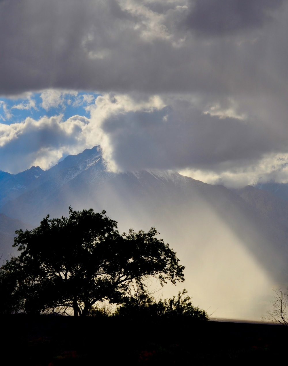 A storm takes turns with the sunset in the valley near Manzanar, CA
