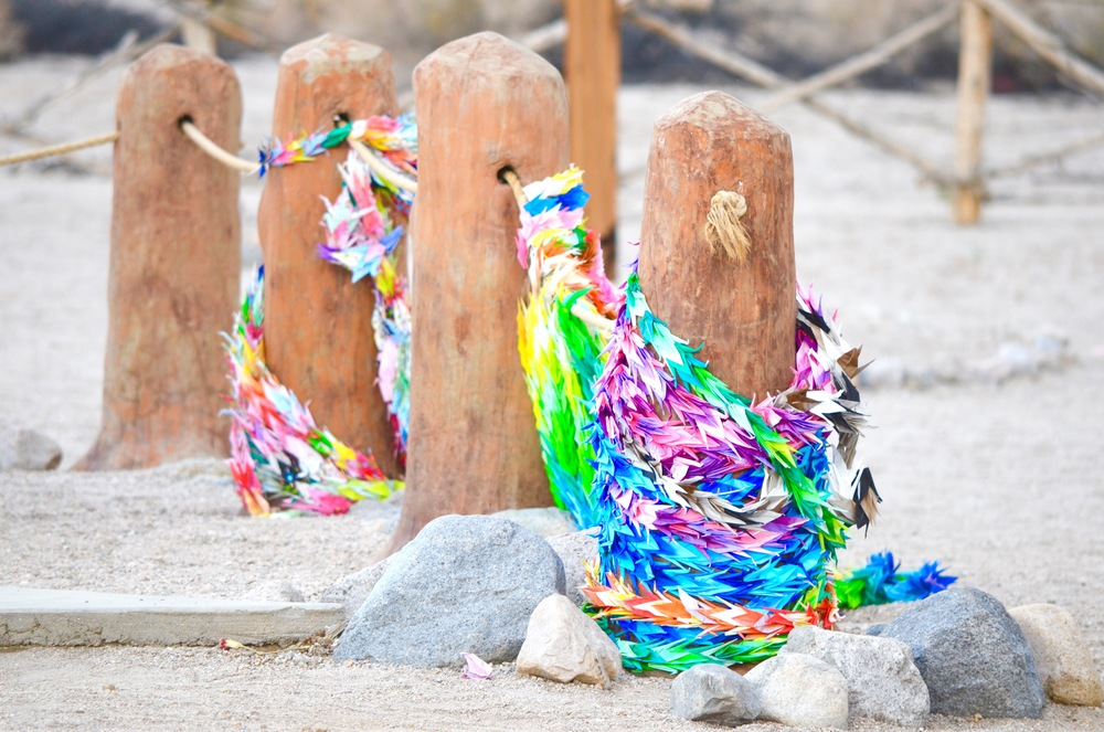 Paper cranes left on the posts at Manzanar cemetery