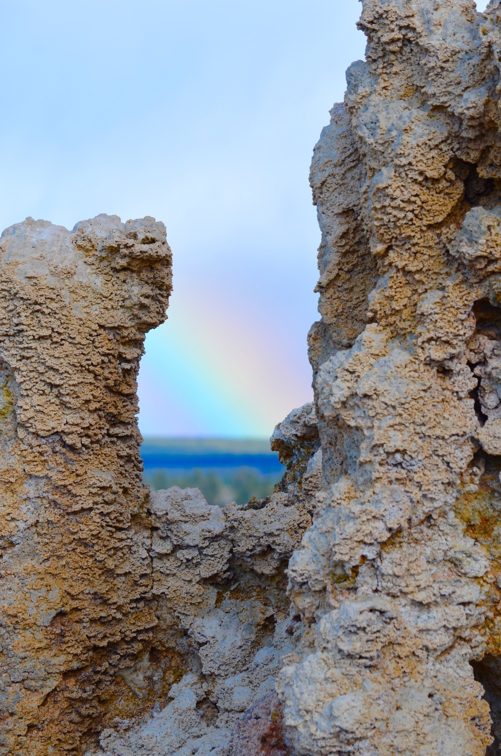 "A rainbow is captured in between the mineral ""tufa"" of Mono Lake. Tufa are created when bubbling springs bring mineral deposits to the surface of the lake."