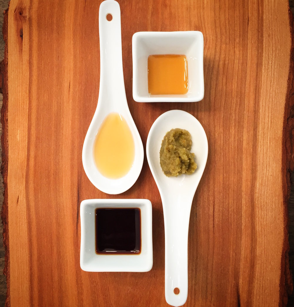 Ingredients for yuzukosho soy salad dressing. Clockwise from top: bourbon-aged maple syrup, yuzukosho paste, soy sauce, sesame oil.