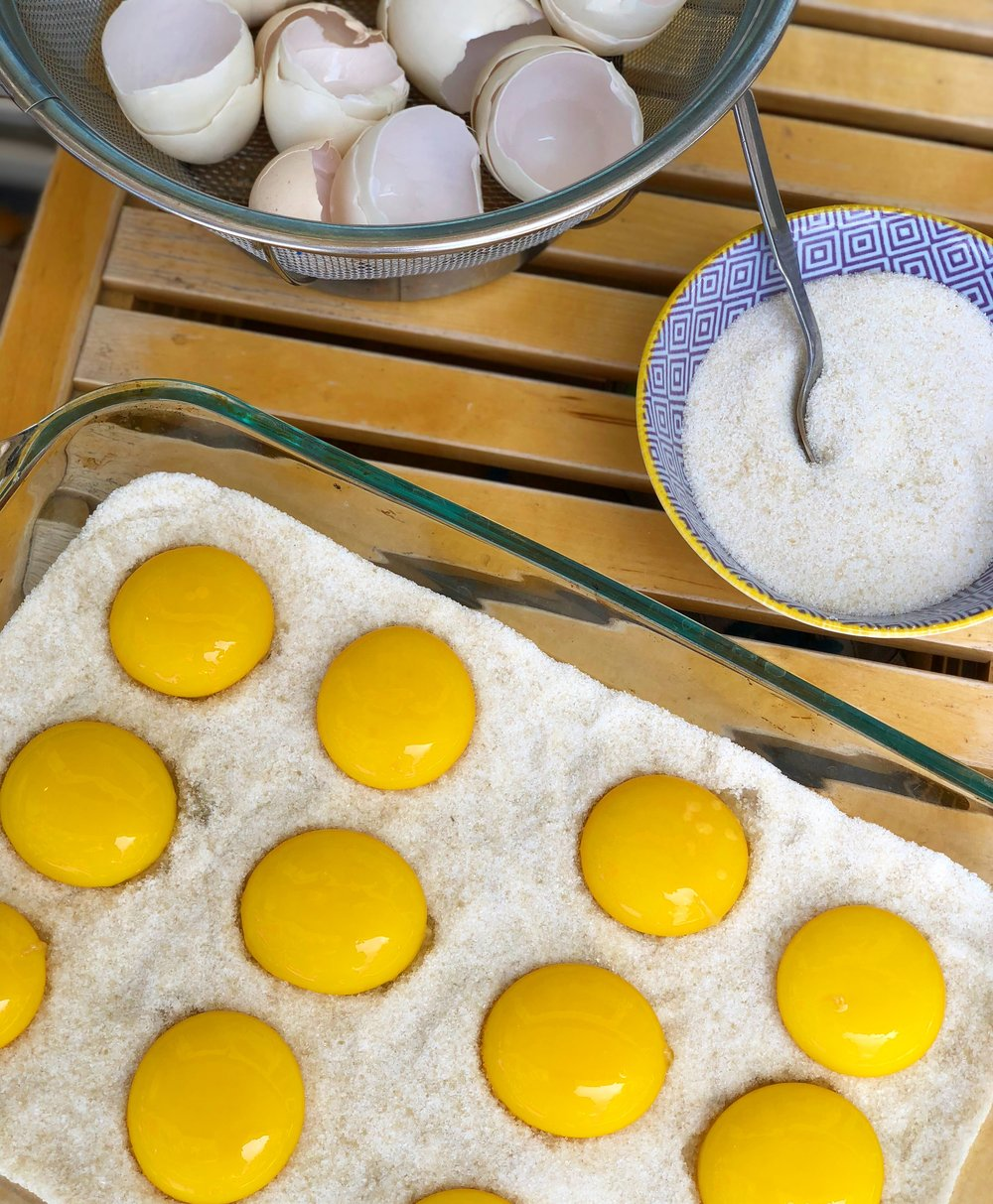 Fresh yolks placed in salt/sugar, covered, and refrigerated.