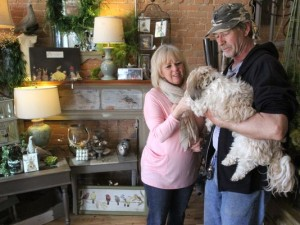 Cathy and Tom Bateman work in the showroom of their store, Encore 118, in downtown Howell. Moose, the couple's dog, left, often spends time at the store.