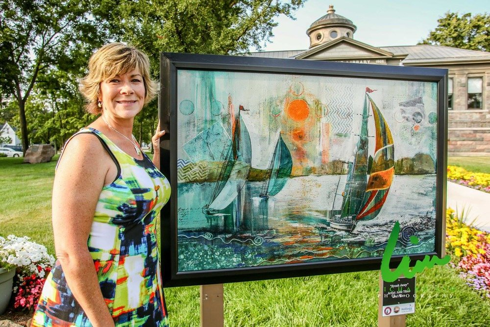 Artist by her sailboart art on library lawn.jpg