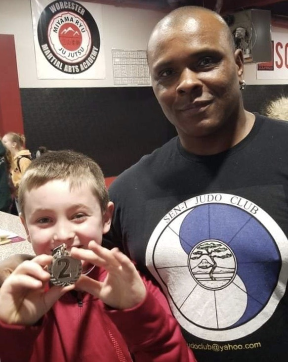 Mason Metcalf-Nale, from Holland, proudly shows off his medal next to Sensei Israel Lopez.