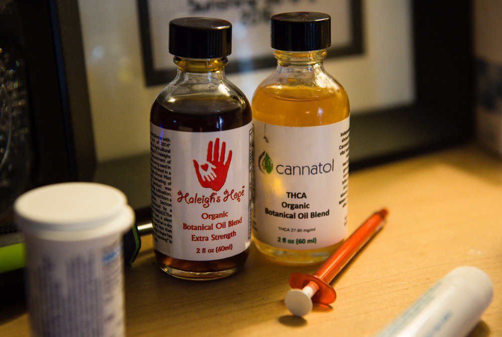 Vials of cannabis oil that Janea uses to treat Haleigh rest on a table in the living room.