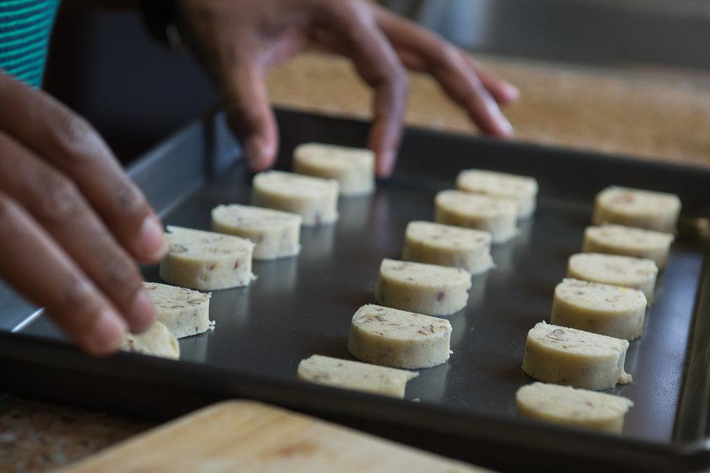 Rosalind Bentley arranges slices of lemon icebox cookie dough on a baking sheet. The recipe belonged to Lucille Burton, Bentley's great aunt and mother to Bentley's second cousin Brenda Webb.