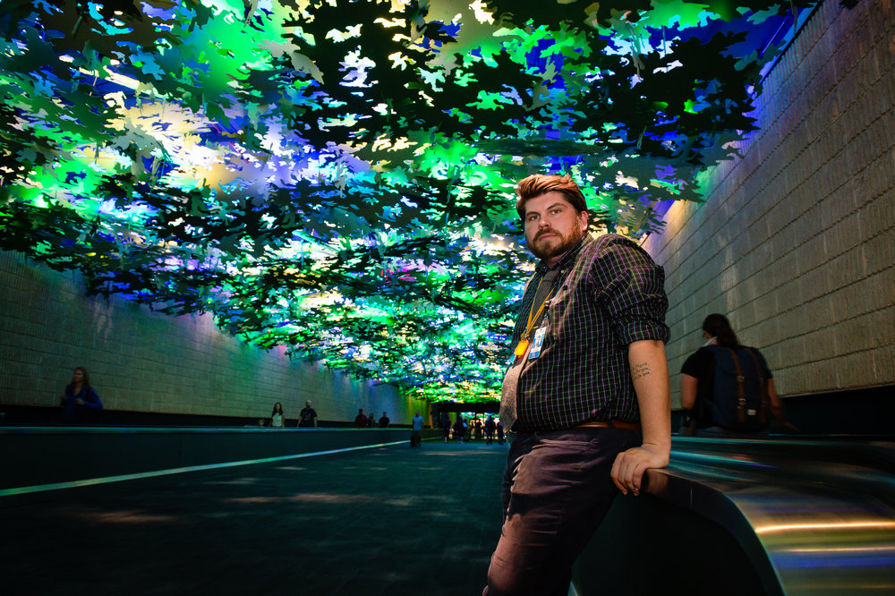 "Art Program Manager Benjamin Austin poses for a photo beneath ""Flight Paths,"" a sculptural tree canopy that covers the walkway between Concourses A and B at Hartsfield Jackson Atlanta International Airport Friday, 28 Sept. 2018."