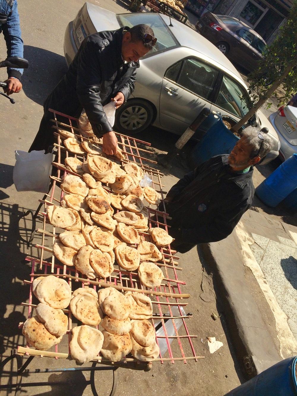 Buying pita bread outside Koshary Abou Tarek in Cairo
