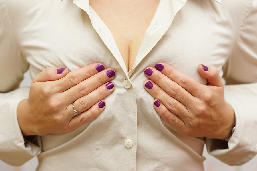 woman holding breasts over cream colored button down shirt