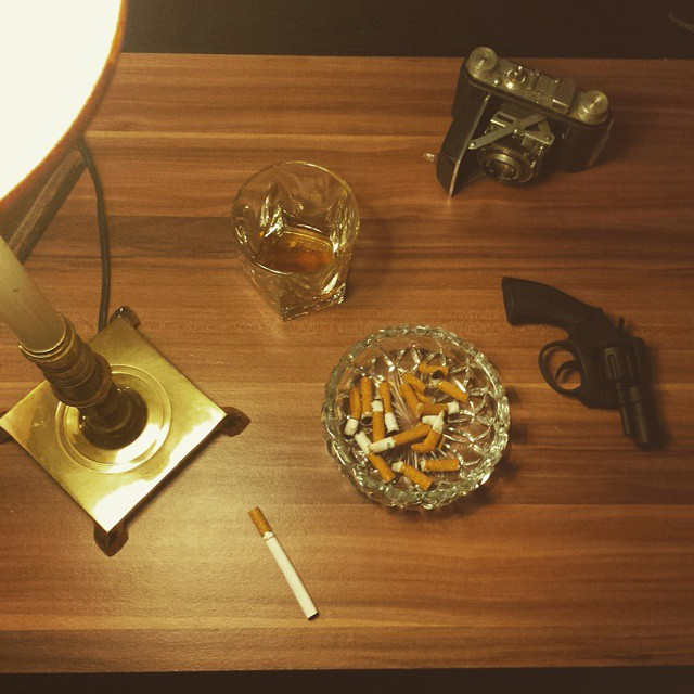 Set design: A thrift store lamp and ashtray; Matt's scotch glass; a friends cigarette butts; my dad's old camera; a Walmart cap gun covered in black spray paint.