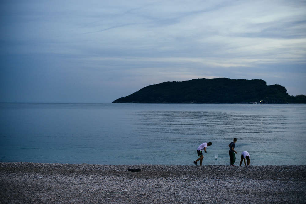 Some local kids skipping rocks into the Adriatic Sea during sunset in Budva.