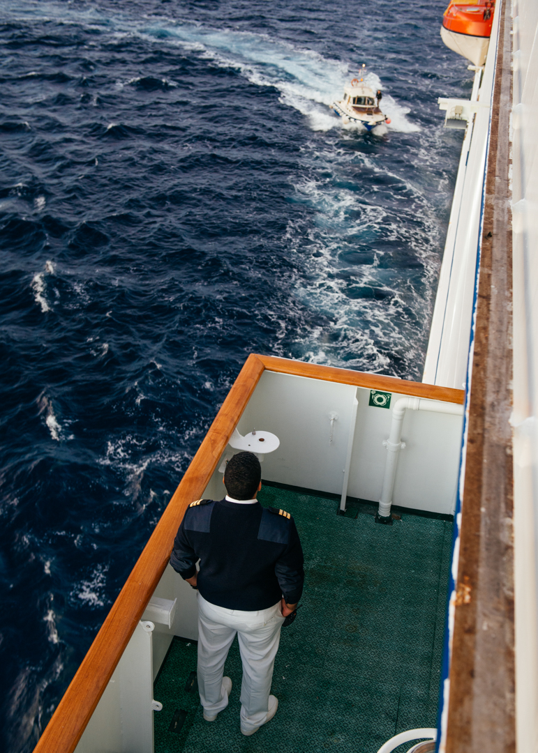 Captain Kostas watches the Pilot approach from the left Bridge to help guide the MV World Odyssey into port.