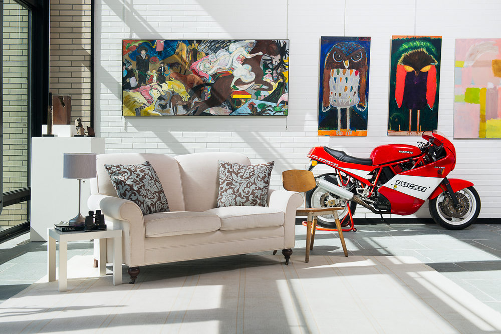 Paintings, sculptures, motorcycles and light fill the gallery space.