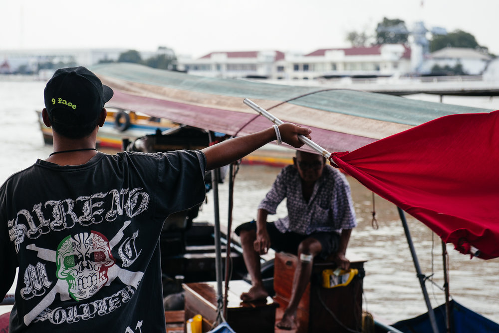 Worker waves in a long-tail boat.