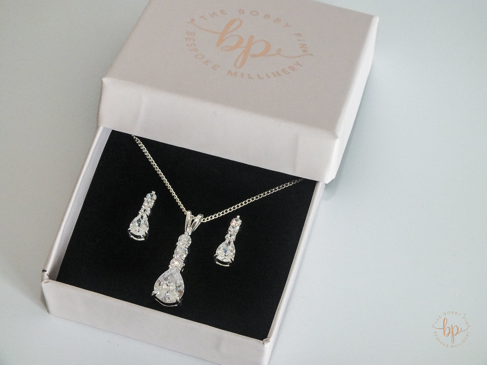 "Bridesmaid Headpieces - The Bobby Pin  Truly stunning bridal necklace and earrings set. This set has four teardrop stones in a sterling silver claw.  The necklace comes with a silver chain. Necklace and earrings match for a perfect look.  The ""Elsa"" necklace and earrings set are made of sterling silver with four cubic zirconia teardrop stones.  This is a classic style for any occasion.  Please note these earrings are only suitable for pierced ears.  Presented in a The Bobby Pin keepsake box.  Dimensions:  Necklace (L) 10mm (W) 20mm  Earrings (L) 6mm (W) 10mm"