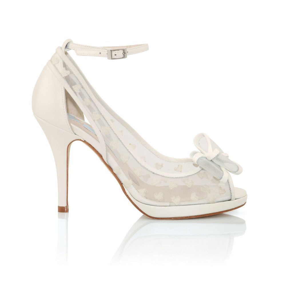 "Bridal Shoes - Charlotte Mills  Alexis Ivory: Heart embroidered mesh peep toe sling back with large structured bow and slim platform. The Alexis bridal shoe in Ivory forms part of Charlotte's signature wedding shoe collection.  INFORMATION  Upper // Ivory leather and mesh with heart embroideries and pale gold buckle.   Lining and sock // Leather/mesh with Charlotte's signature silver sixpence. The left shoe in every pair includes an original silver sixpence to bring you luck on your special day.  Sole // leather embossed with the phrase ""Something old, Something new, Something borrowed, Something Blue and a silver sixpence in her shoe""  One pair of Alexis Bridal shoes in size 36-41"