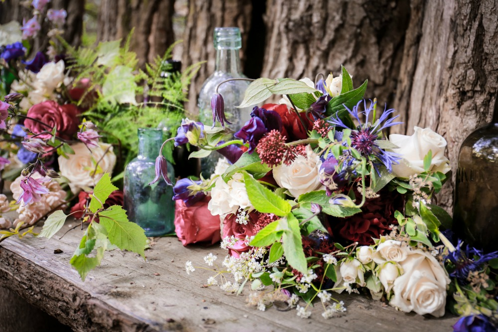 rustic wedding flowers with bottles.jpg