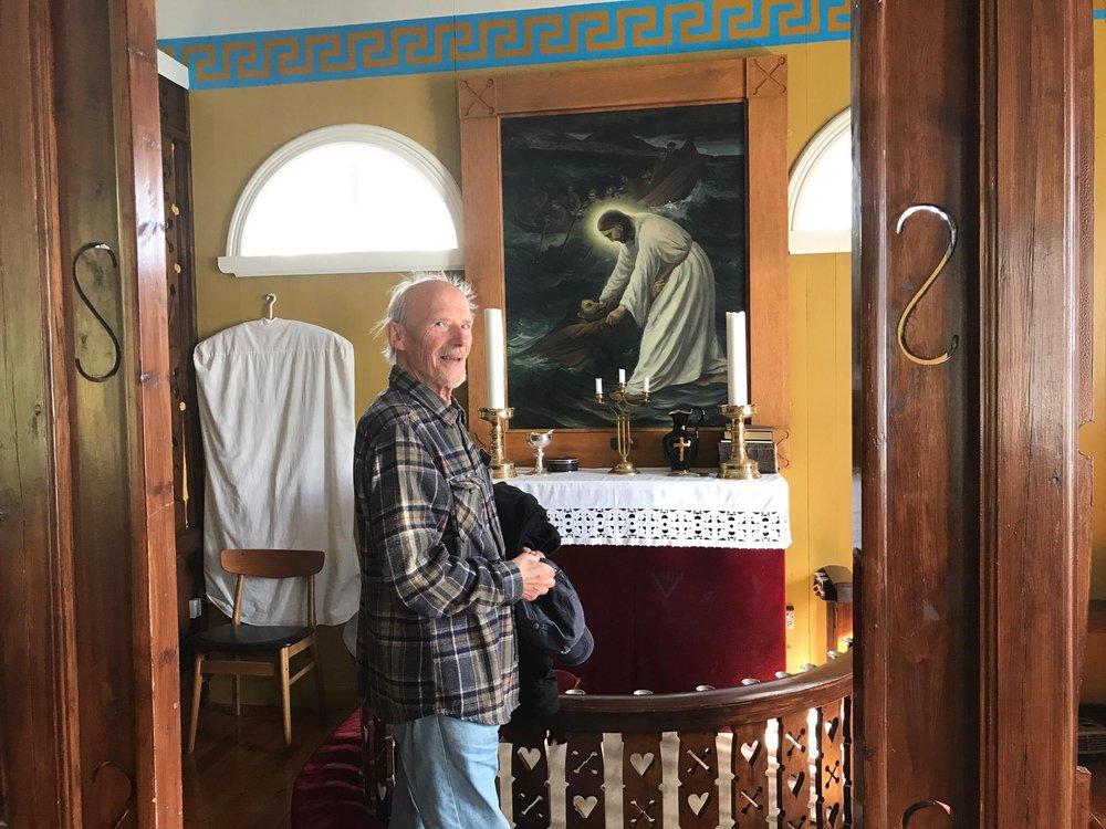 Her er Zacharias Heinesen avmyndaður í kirkjuni á Kirkju framman fyri altartalvu hjá Mikines Foto: Símun Gullaksen