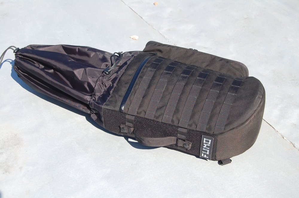 A semi-rigid tactical violin case designed to carry a hard case with attachment points for accessories.