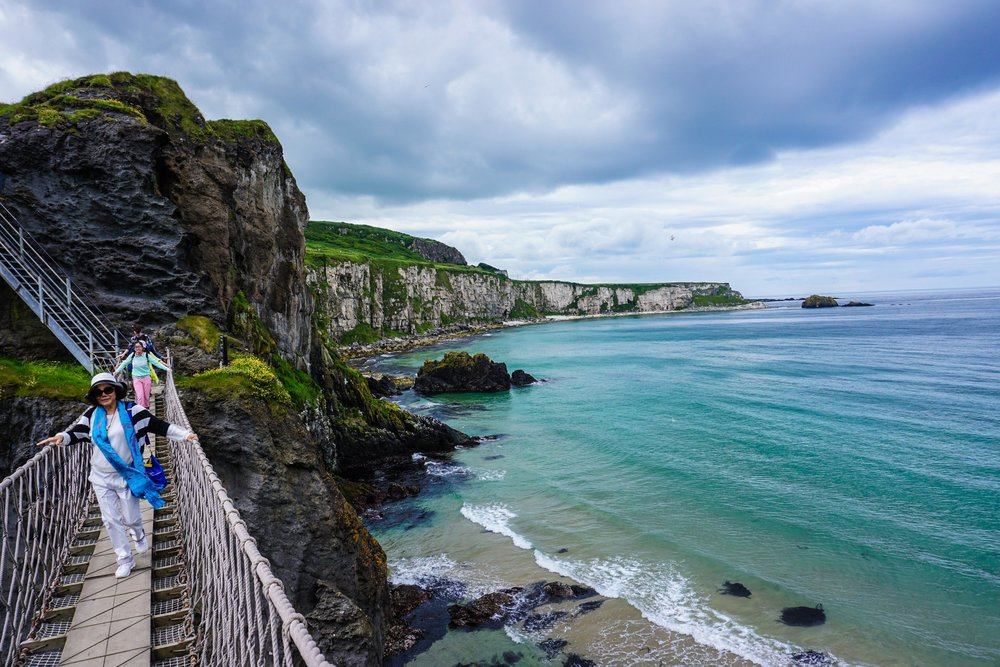 Carrick-a-Rede being traversed by a hard-worn and earth-wise adventurer