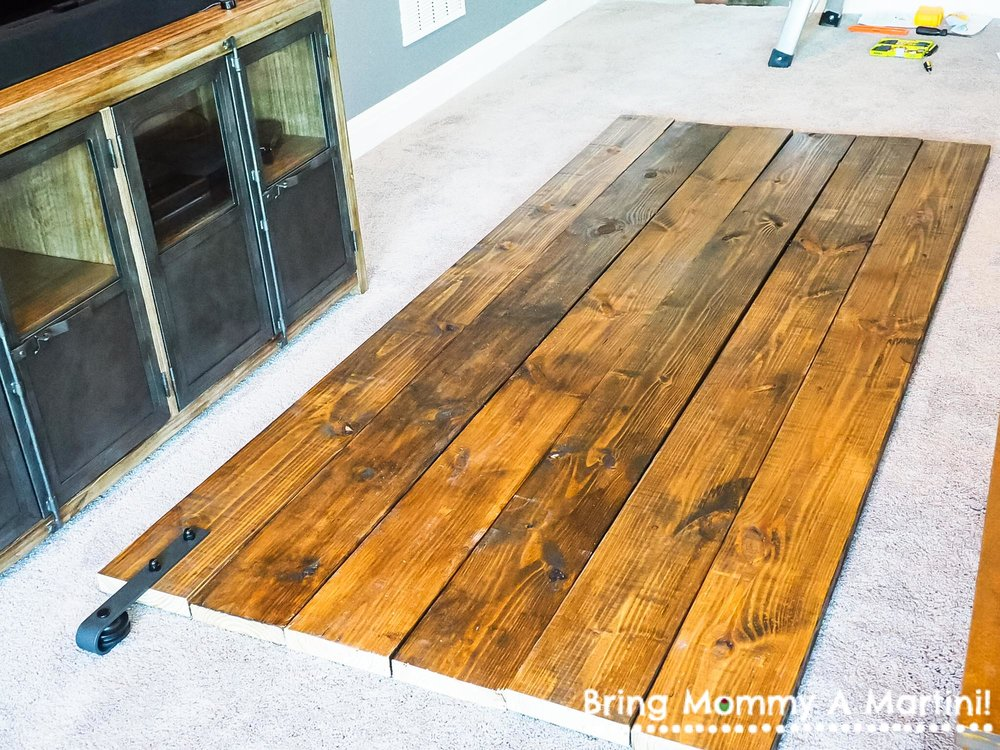 "Next, we arranged the wood how we wanted it to look - balancing out dark pieces and light ones. We wanted a few cross pieces, too, and our plan was to use a 7th plank, cut into shorter pieces, but they were way too wide and thick and didn't look right. We went back to Lowe's for a few planks of 1x6"" pine to use as our horizontal pieces."