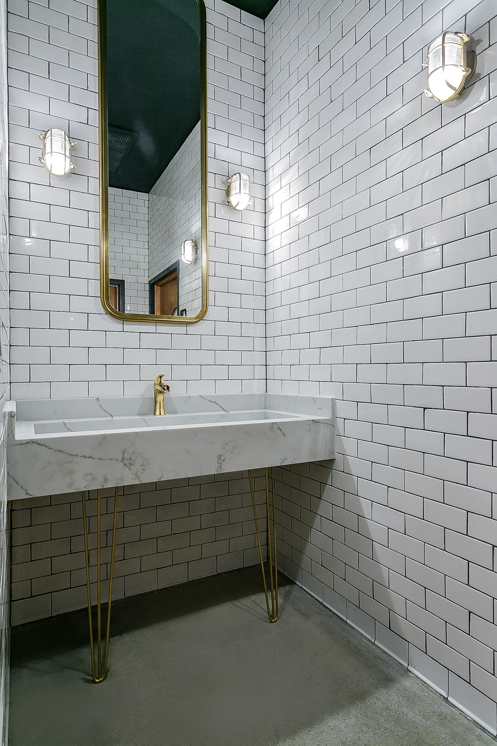 melrose-station-speakeasy-bar-in-hollywood-by-archillusion-design-los-angeles-restroom-custom-marble-sink-midcentury-brass-legs-brass-mirror-brass-lights