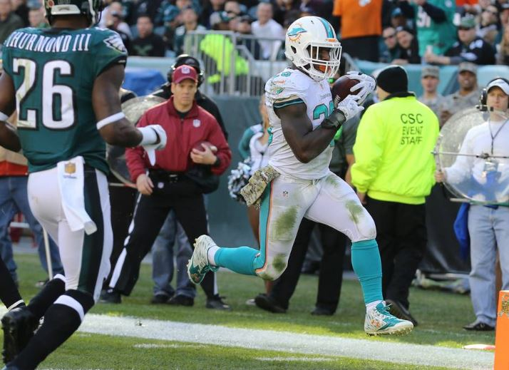 Lamar Miller scores on a pass against the Eagles