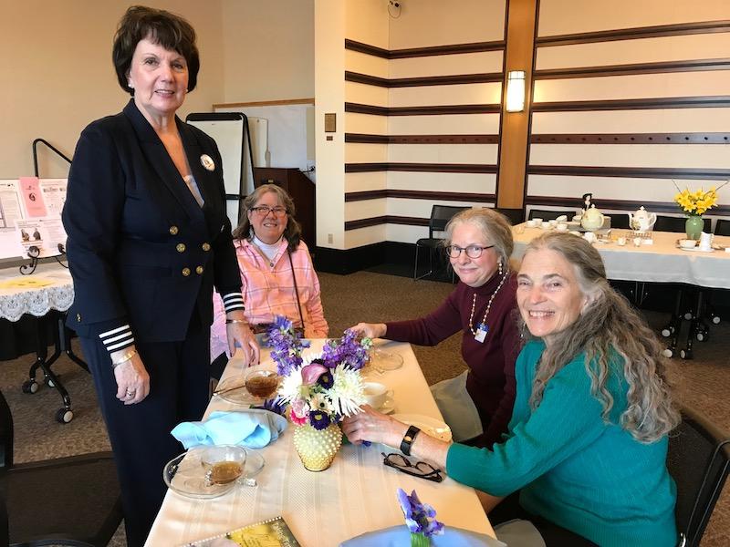 Volunteer coordinator Kathy Krusiek (standing) with guests enjoying high tea.