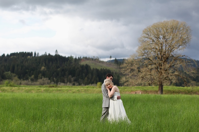 Bride and groom hugging in field