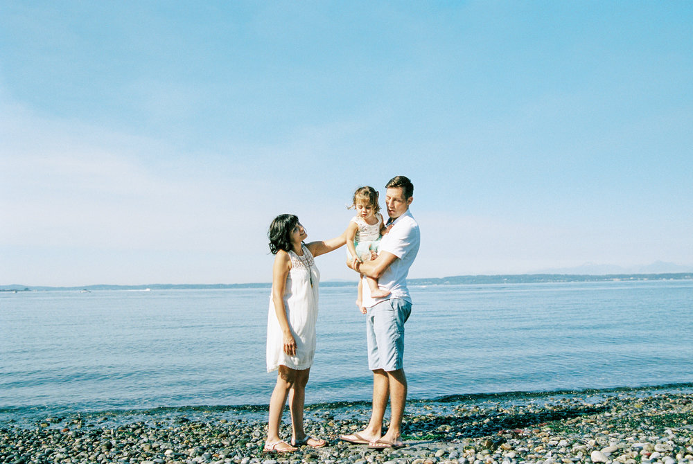 Seattle family film photographer photos photo girl daughter mom dad ocean pudget sound waves sand driftwood light sun newborn new born