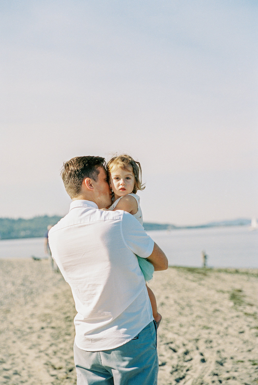Seattle family film photographer photos photo girl daughter mom dad ocean pudget sound waves sand driftwood light sun newborn new born daddy daughter dad
