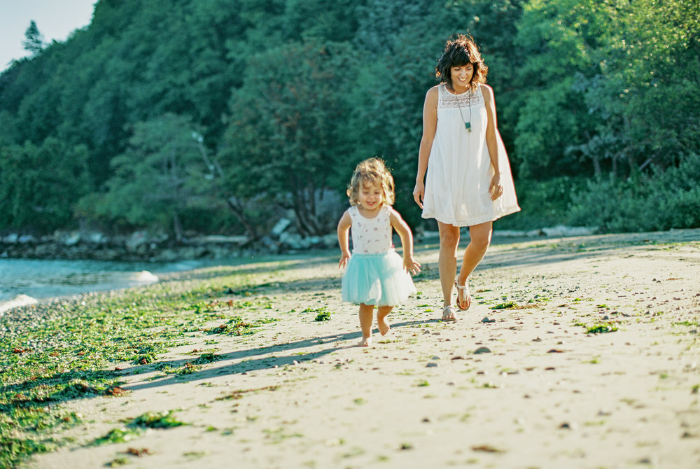 Seattle family film photographer photos photo girl daughter mom dad ocean pudget sound waves sand driftwood light sun newborn new born mother daughter walking on beach